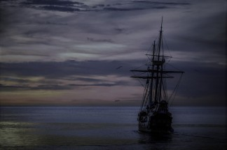 sunset-boat-sea-ship-37730.jpeg old ships in a cloudy but still waters